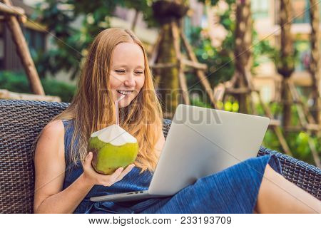 Young Female Freelancer Sitting Near The Pool With Her Laptop In The Hotel Browsing In Her Smartphon