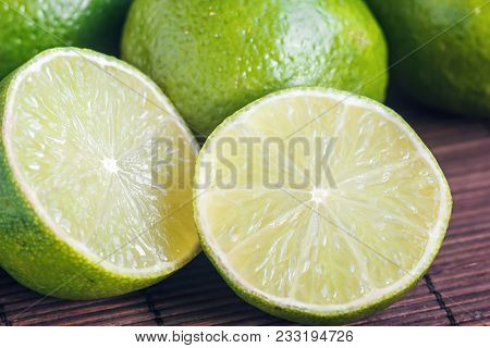 Lime Citrus Fresh Fruits On Wooden Table. Close Up Shot Of Limes. Focus On The Central Part Of Slice
