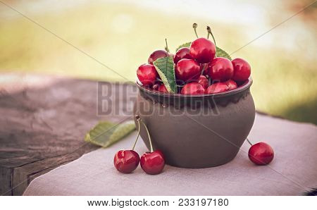 Cherries In Ceramic Bowl And Kitchen Napkin On Wooden Background. Red Cherry With Leaves In Sunlight
