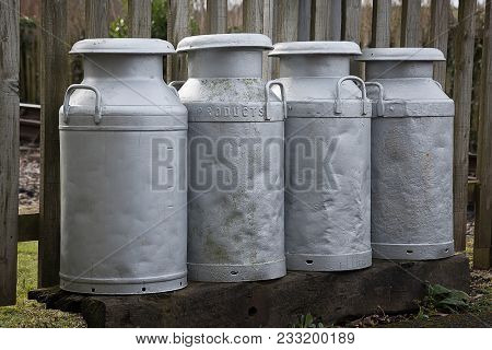 A group of four old fashioned metal milk churns showing signs of heavy usage. introduced in the 1930s held ten gallons. The use of churns ceased in Britain in 1979 poster