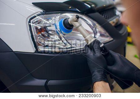 Auto Mechanic Buffing And Polishing Car Headlight Car Detailing - Man With Orbital Polisher In Auto