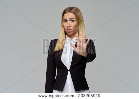 A Frustrated Young Business Woman Frowns Her Eyebrows And Shows A Sign Of Refusal With Her Hand, Ask