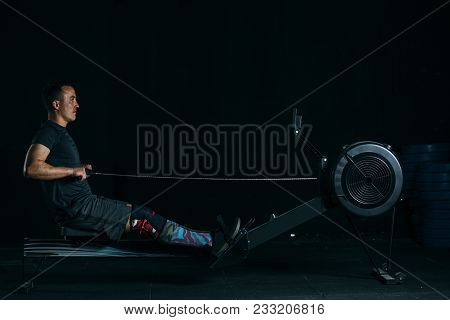 Side View Of A Young Sporty Man Doing Rowing Exercise On A Fitness Routine At The Box Gym