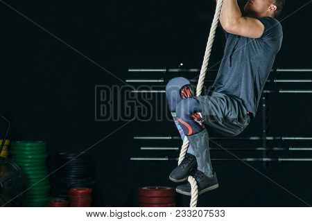 Cropped View Of A Side View Of A Young Sporty Man Doing Rope Climb Exercise On A Fitness Routine At