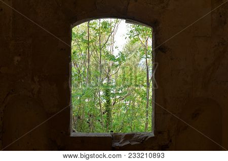 Arched Old Window Of An Old Abounded Fortress With A View To A Abounded Garden Tress