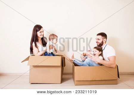 Family Unpacking Cardboard Boxes At New Home And Have Fun