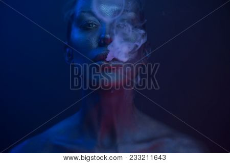 Halloween Vape Party, Nightlife. Beautiful Sexy Young Woman with glamorous mystical makeup vaping in Nightclub, exhaling smoke. Girl smoking vaporizer in Club. Blue mystic smoke poster