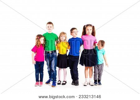 The Happy Kids Are Standing Together Embracing Each Other In Colorful Clothes Isolated On White Back
