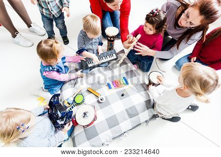 Moms With Children At The Music Lesson In The Kindergarten. Preschoolers Are Studying Musical Instru