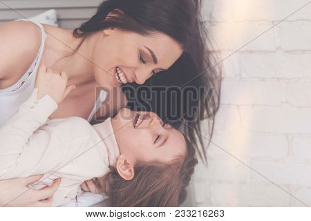 My Favorite Smile. Hilarious Engaging Charismatic Family Smiling And Hugging In Bed While Enjoying T