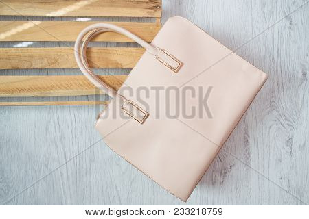 Fashionable Concept. Beige Handbag. Twooden Box On The Background.