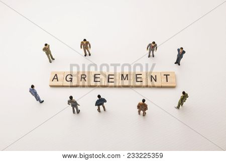 Miniature Figures Businessman : Meeting On Agreement Letters By Wooden Block Word On White Paper Bac