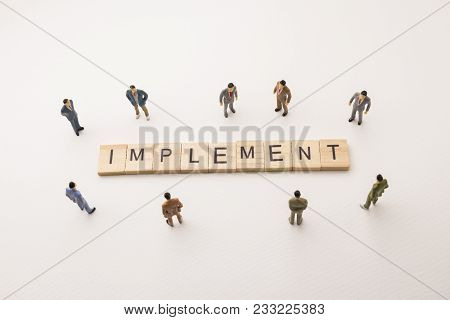 Miniature Figures Businessman : Meeting On Implement Letters By Wooden Block Word On White Paper Bac