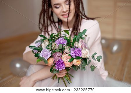 Smiling woman with dreadlocks hairstyle showing a bouquet of flowers in hands indoors. Focus on flowers with blurred woman on background. poster