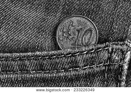 Euro Coin With A Denomination Of 10 Euro Cents In The Pocket Of Worn Denim Jeans, Monochrome Shot.
