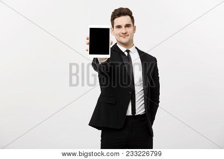 Business Concept: Smiling Handsome Businessman Presenting Website Or Presentation On Tablet