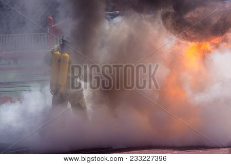 Firefighter In Equipment Extinguishes Fire With A Fire Extinguisher