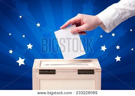 Voting hand with ballot and wooden box