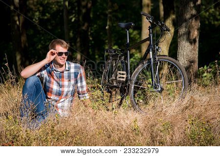 The Young Guy Wearing Jeans And A Shirt In A Section Sits On A Dry Grass In The Wood During Bicycle