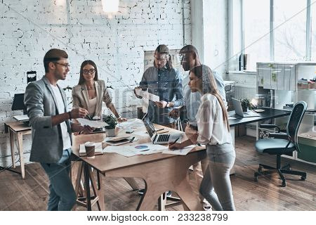 Team Of Innovators. Group Of Young Modern People In Smart Casual Wear Discussing Business While Stan