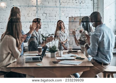 Real Success. Modern Young Business People Clapping And Smiling While Working Behind The Glass Wall