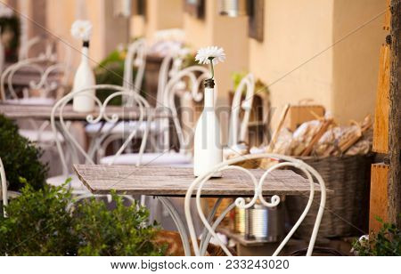 Cozy terrace on an italian street with white chairs and white flowers