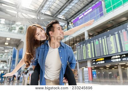 Young Asian Couple Having Fun And Playing At Airport Terminal. Happy Asia Lovers Are Traveling Honey