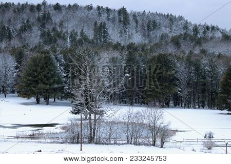 A Pond And Fence With A Snow Covered Field And Trees.