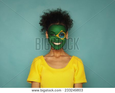 Portrait Of A Woman With The Flag Of Brazil Painted On Her Face. Football Or Soccer Team Fan, Sport
