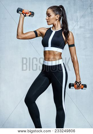 Sporty Woman Does The Exercises With Dumbbells. Photo Of Muscular Woman In Sportswear On Grey Backgr