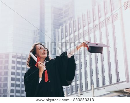 Graduation Day, Young Woman With Graduation Cap And Gown Holding Diploma, Successful Concept