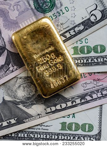 Cast Gold Bar Weighing 250 Gram Against The Background Of Dollar Bills.