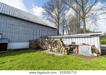 Barnyard With Green Grass And A Woodstack On A Sunny Day