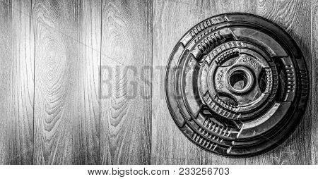 Heavy Barbell Plate Weight On The Gym Floor Ready For Strength Bodybuilding Workout