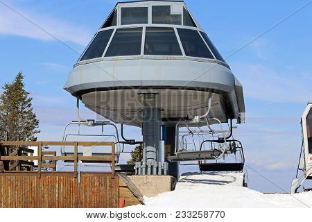 An Elevated Passenger Ski Chairlift With A Blue Sky Background.