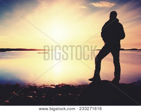 Silhouette Of Alone Man Looking Toward Vibrant Sunset. Flare And  Reflected In Shallow Waters Of Sea