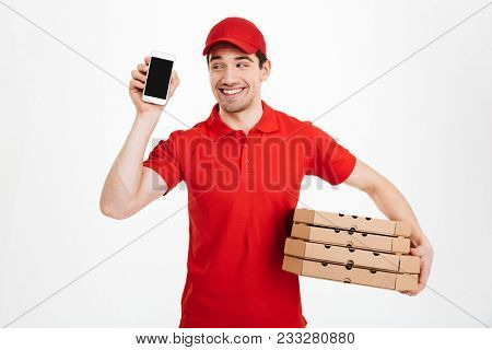 Delivery man in red t-shirt and cap holding stack of pizza boxes and showing copyspace screen of cell phone meaning call or text isolated over white background