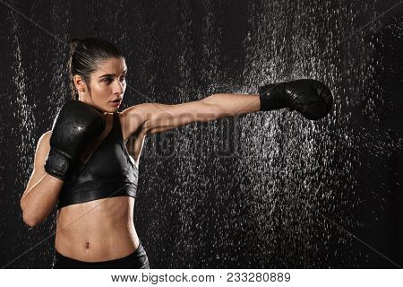 Female fighter 20s with perfect body in sportswear and black boxing gloves throwing strong punch under rain drops isolated over dark background