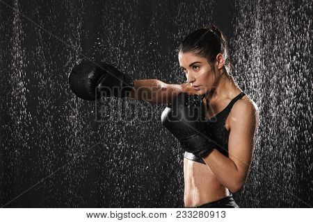 Female fighter 20s in sportswear and black boxing gloves throwing punches under rain drops isolated over dark background