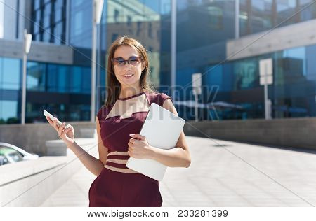 Happy Successful Businesswoman In Sunglasses With Laptop Outdoors. Caucasian Executive Taking A City
