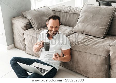 Laughing mature man talking on mobile phone while sitting on a floor with laptop computer and drinking coffee in a living room