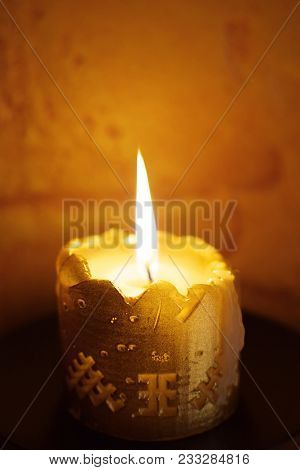 One Half -burned Candle Light In The Dark. Burning Candle On Dark Blur Background.