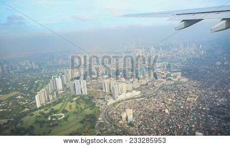A View Of The City Of Manila Through The Window From The Plane. Impressed Photo Of A Tourist In Flig