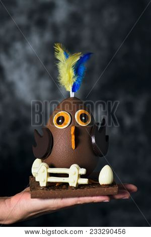 closeup of a funny chocolate chick as a spanish mona de pascua, a traditional confection given by godparents to godchild on Easter and typically eaten on Easter Monday, in the hand of a young man