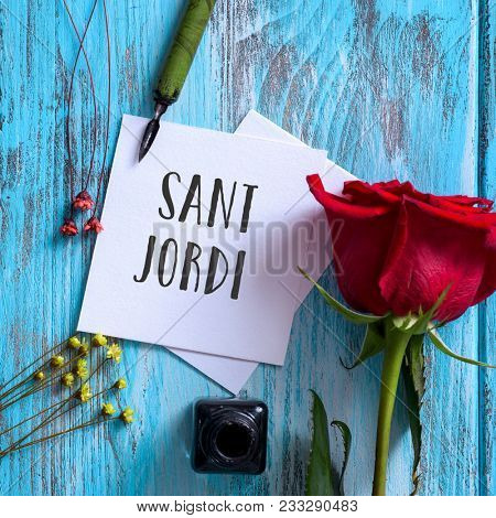 high angle view of a red rose, an ink bottle, a nib pen and the text Sant Jordi, the name of Saint George Day in Catalan, when it is tradition to give red roses and books in Catalonia, Spain