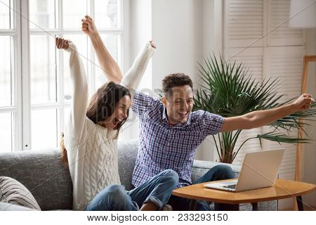Excited Man And Woman Screaming With Joy Raising Hands Looking At Laptop Screen Sitting On Sofa At H