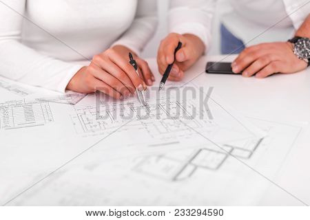 Employees Work On Blueprints Or Engineering Plans In The Office. Engineering. Teamwork.