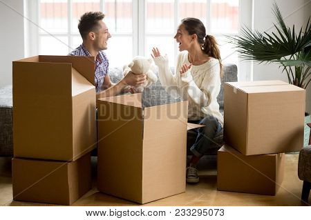 Young Happy Couple Having Fun Packing Boxes On Moving Day, Loving Boyfriend Making Gift Holding Cute