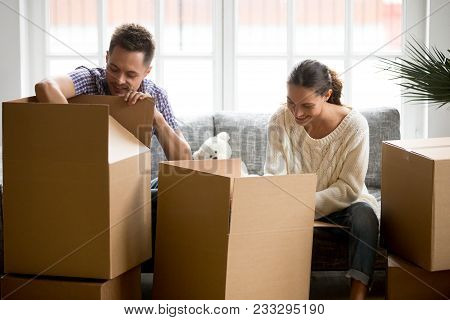 Young Smiling Couple Unpacking Cardboard Boxes Together Sitting On Sofa In Modern Living Room, Movin