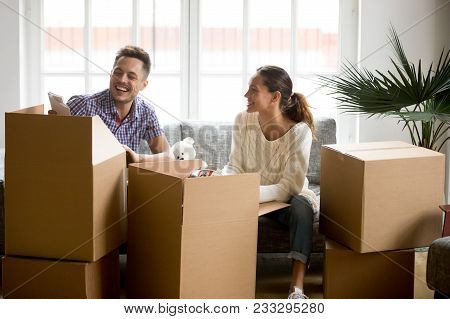 Happy Couple Having Fun And Laughing While Unpacking Boxes On Moving Day, Smiling Young Family Packi